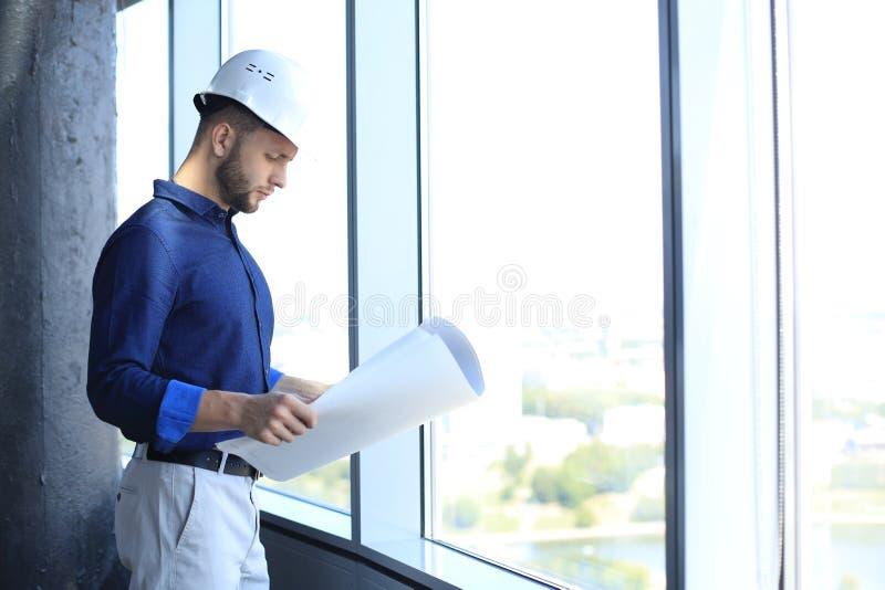 Młody mężczyzna w koszuli, badający plan, stojąc przy oknie w biurze fotografia royalty free