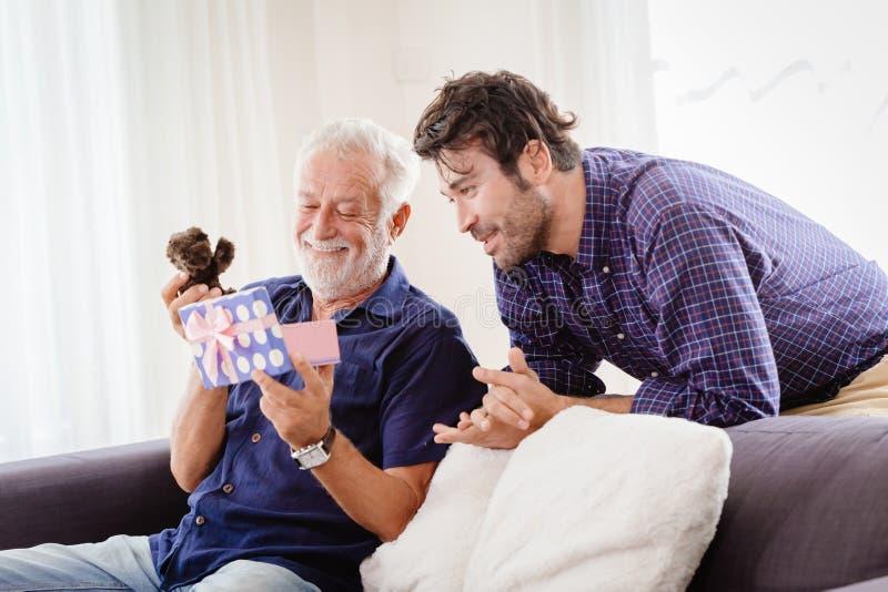 Młody mężczyzna wrócił do domu rodzinnego podczas noworocznego urlopu z uroczym pudełkiem na prezent dla staruszka, Elder uśmiech zdjęcie stock