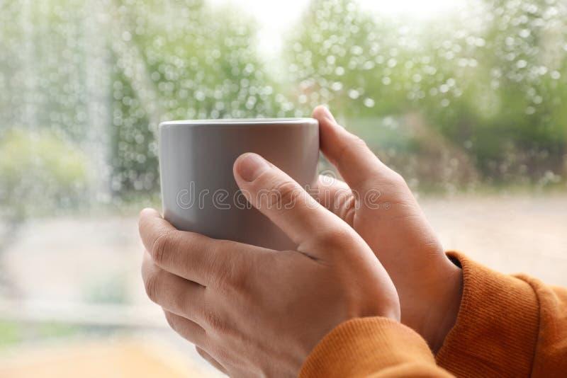 MÅ'ody mężczyzna z filiżankÄ… kawy w pobliżu okna w deszczowym dniu zdjęcie royalty free