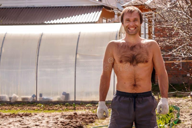 Młody męski średniorolny ono uśmiecha się szczęśliwie w ogródzie zdjęcia stock