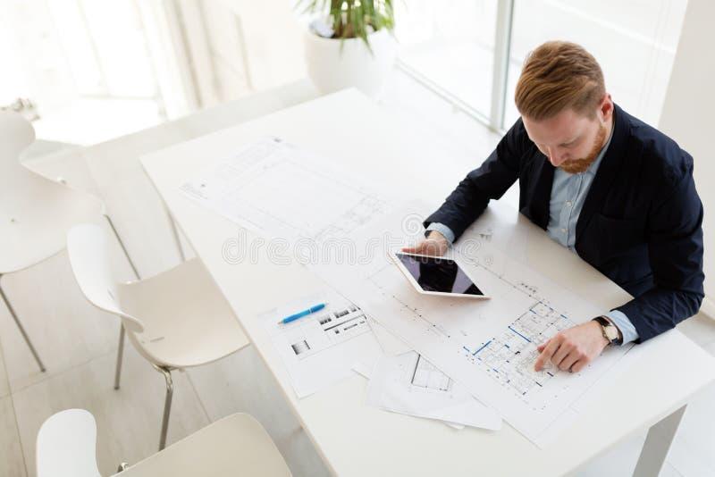 Młody męski architekt pracuje na projekcie w biurze fotografia stock