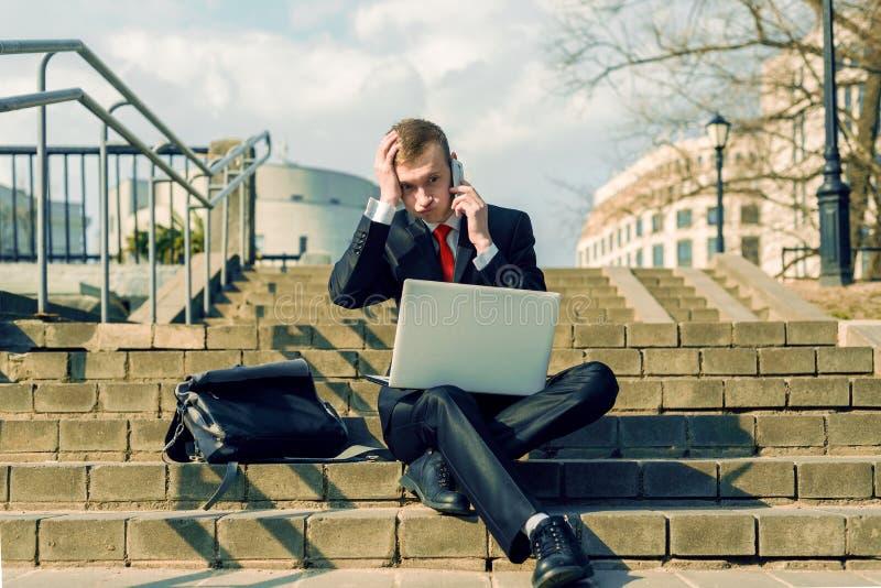 Młody męski biznesmen opowiada na telefonie na ulicie męski freelancer w czarnym kostiumu i czerwonym krawacie siedzi z laptopem obraz stock