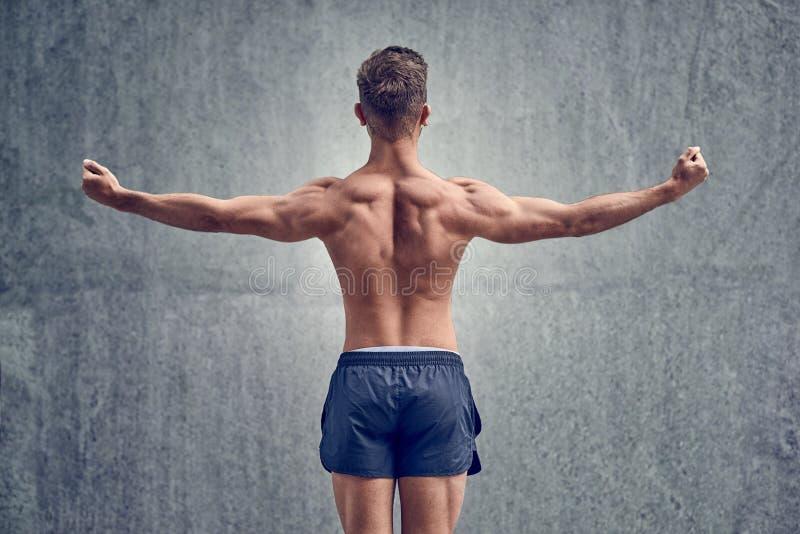 Młody męski bodybuilder pozuje przed ścianą zdjęcie royalty free