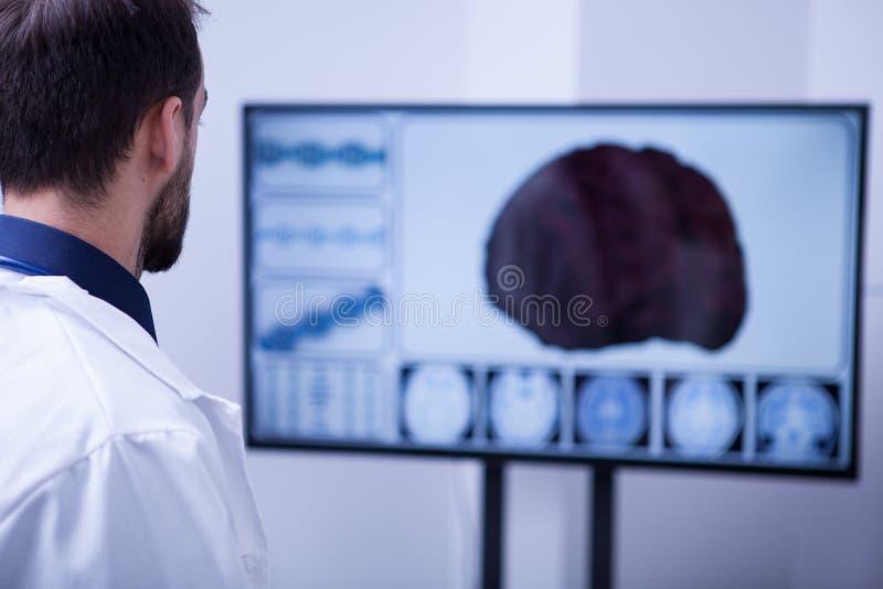 Młody męski chirurg używa technologię sprawdzać za cierpliwym mózg fotografia royalty free