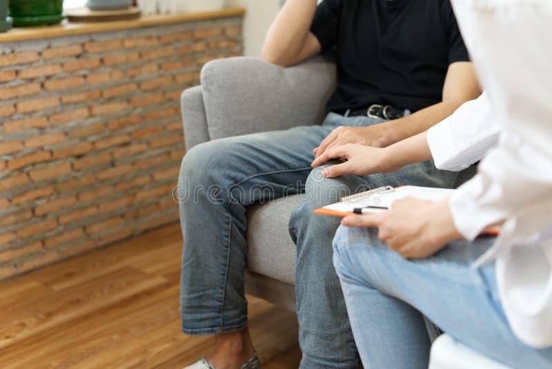 Młody męski cierpliwy obsiadanie na kanapie z smutną twarzą konsultuje z psychologiem fotografia royalty free