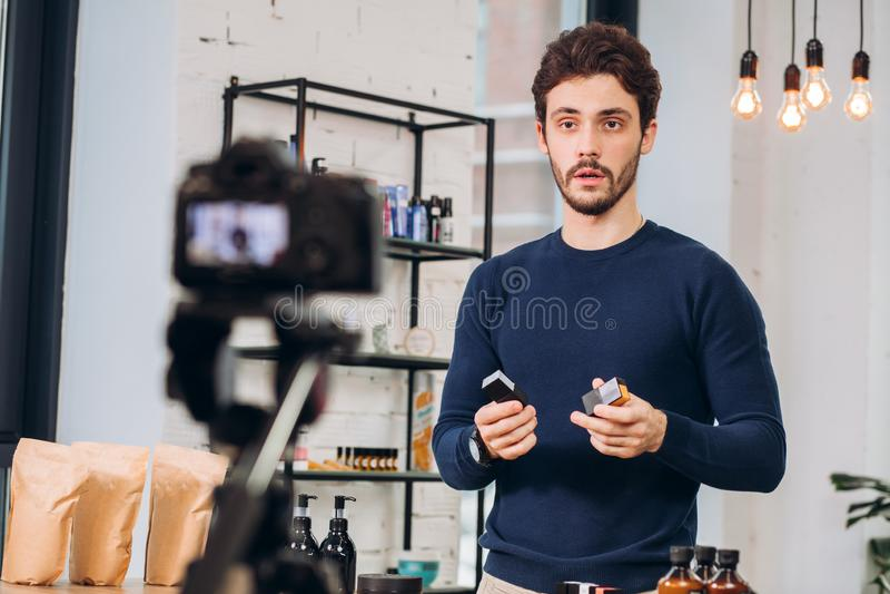 Młody męski cosmetologist tworzy film o kosmetykach zdjęcia stock