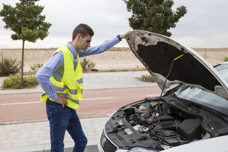 Młody męski kierowca jest ubranym odbijającą kamizelkę, sprawdza samochodowego silnika obraz royalty free