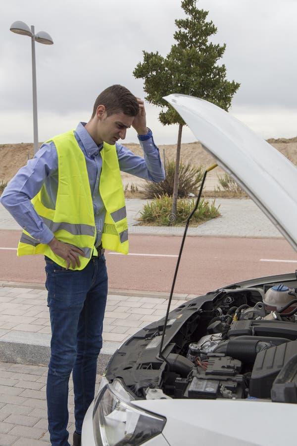 Młody męski kierowca jest ubranym odbijającą kamizelkę, sprawdza samochodowego silnika zdjęcia royalty free