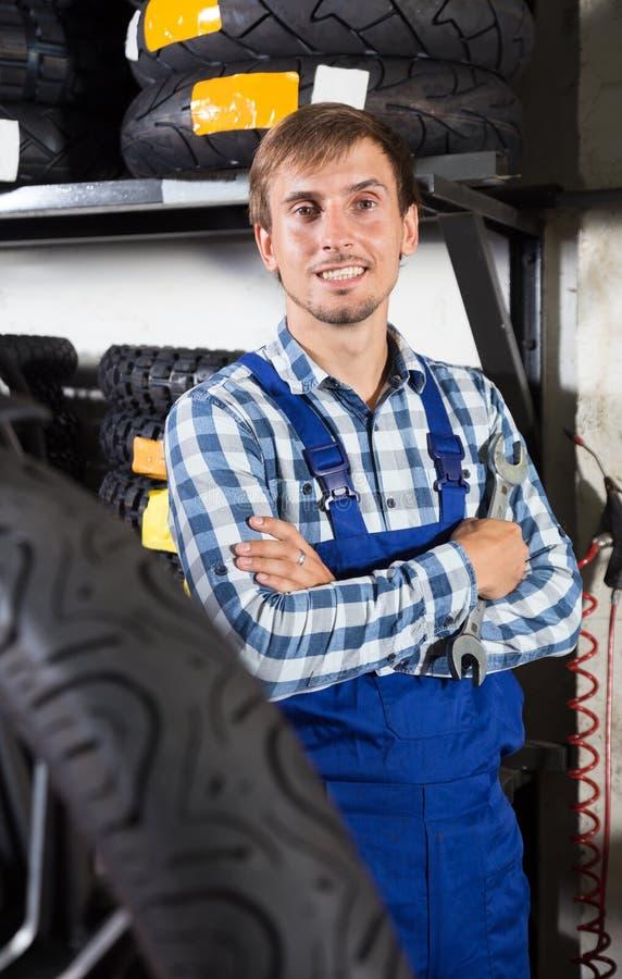 Młody męski mechanik pracuje w auto remontowym sklepie fotografia royalty free