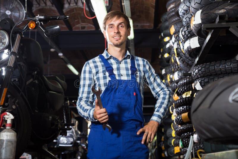 Młody męski mechanik pracuje w auto remontowym sklepie obrazy stock