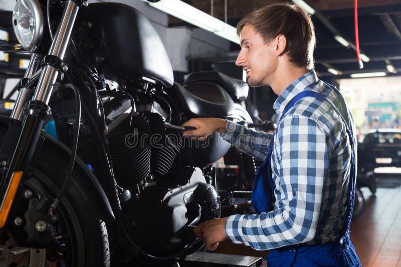 Młody męski mechanik pracuje w auto remontowym sklepie zdjęcie royalty free