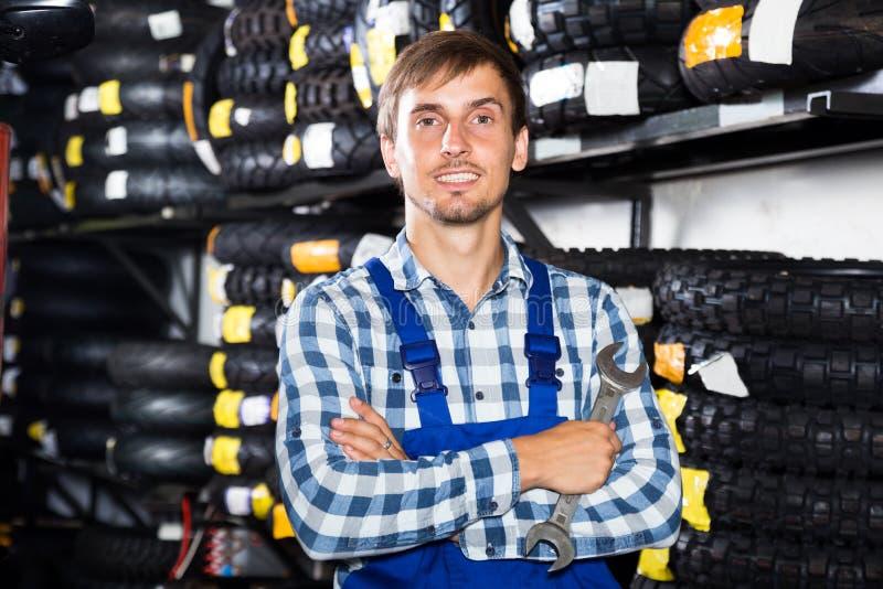 Młody męski mechanik pracuje w auto remontowym sklepie zdjęcia royalty free