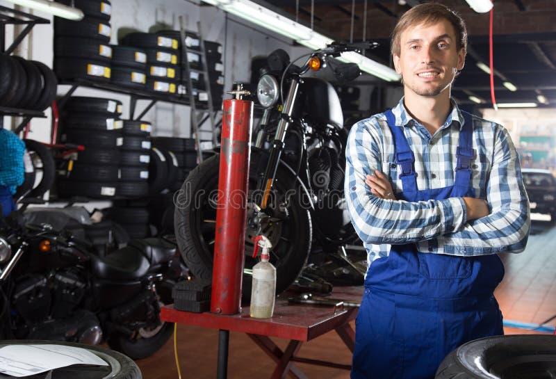 Młody męski mechanik pracuje w auto remontowym sklepie zdjęcie stock