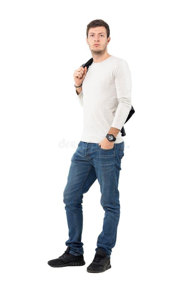 Młody męski moda model w przypadkowych ubraniach niesie skórzaną kurtkę nad ramieniem fotografia stock