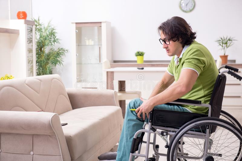 Młody męski nieważny w wózku inwalidzkim cierpi w domu obrazy stock