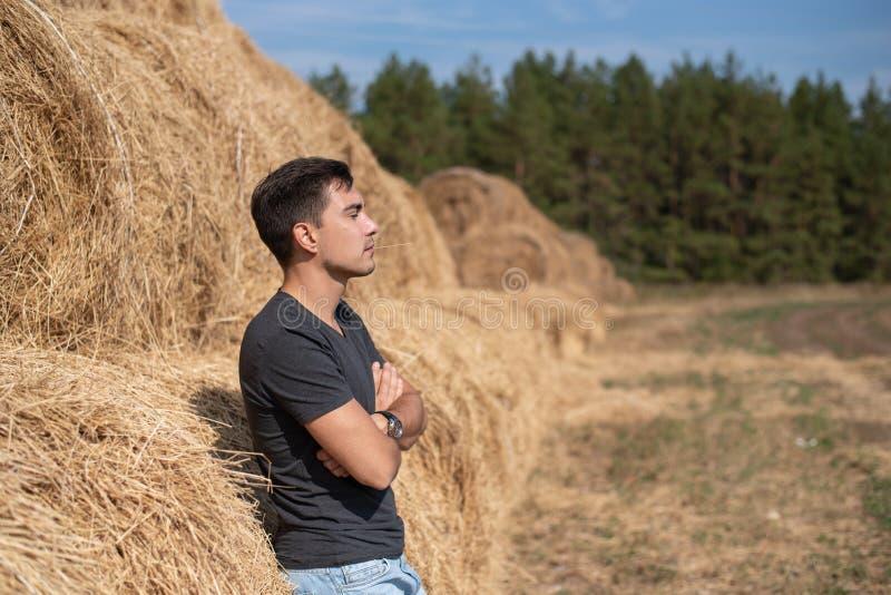 Młody męski rolnik patrzeje strona w popielatej koszulki pozyci przy haystack, kopii przestrzeń zdjęcie royalty free