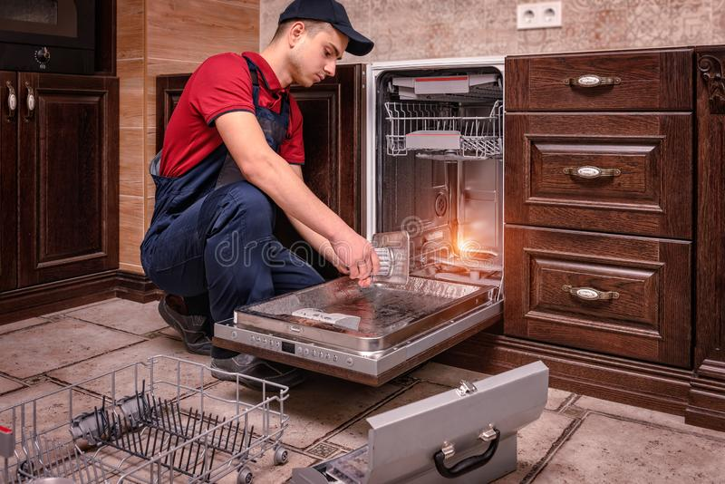 Młody Męski technika naprawiania zmywarki do naczyń W kuchni obraz stock