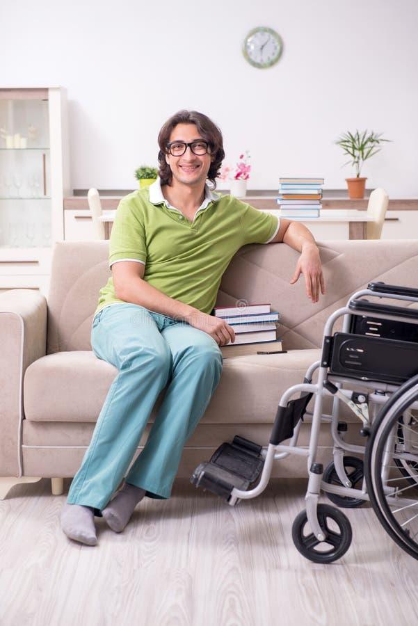 Młody męski uczeń w wózku inwalidzkim w domu zdjęcia royalty free