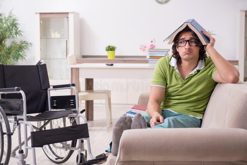 Młody męski uczeń w wózku inwalidzkim w domu obraz royalty free