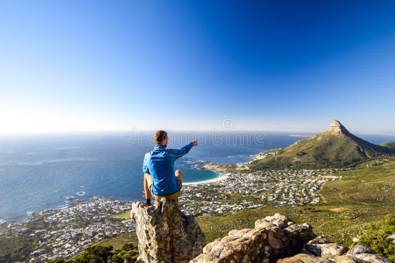 Młody męski wycieczkowicza obsiadanie na skale przy Kasteelspoort Wycieczkuje ślad w Stołowym Halnym parku narodowym w Kapsztad zdjęcie royalty free