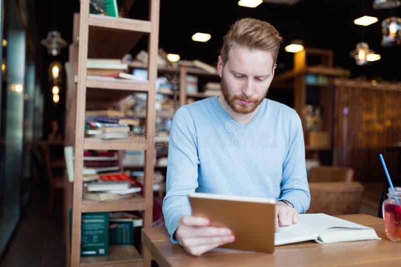 Młody męskiego ucznia czytanie w sklep z kawą obraz royalty free