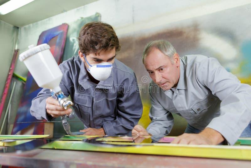 Młody malarz używa kiść pistolet pod mistrzowską inwigilacją obrazy stock