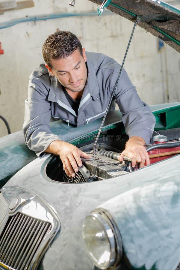 Młody mechanik naprawia starego samochodowego silnika obraz royalty free