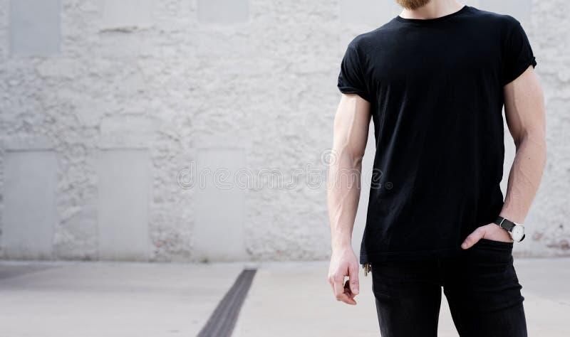 Młody mięśniowy brodaty mężczyzna jest ubranym czarnego tshirt i cajgi pozuje outside Biała cegły ściana na tle zdjęcie stock