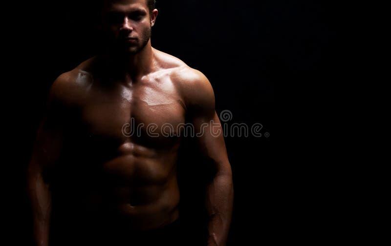 Młody mięśniowy dysponowany sportowa pozować bez koszuli na czarnym backgroun zdjęcie royalty free