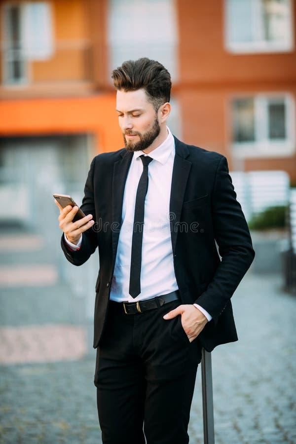 Młody miastowy fachowy mężczyzna używa mądrze telefon Biznesmena mienia mobilny smartphone używać app sms texting wiadomość obraz royalty free