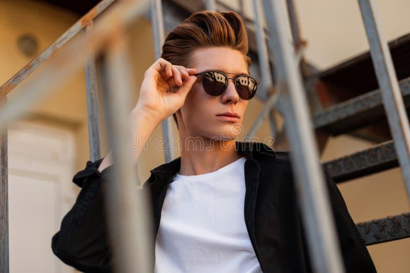 Młody miastowy modnisia mężczyzna prostuje modnych czarnych szkła Portret elegancki przystojny facet w czarnej rocznik koszula zdjęcia stock