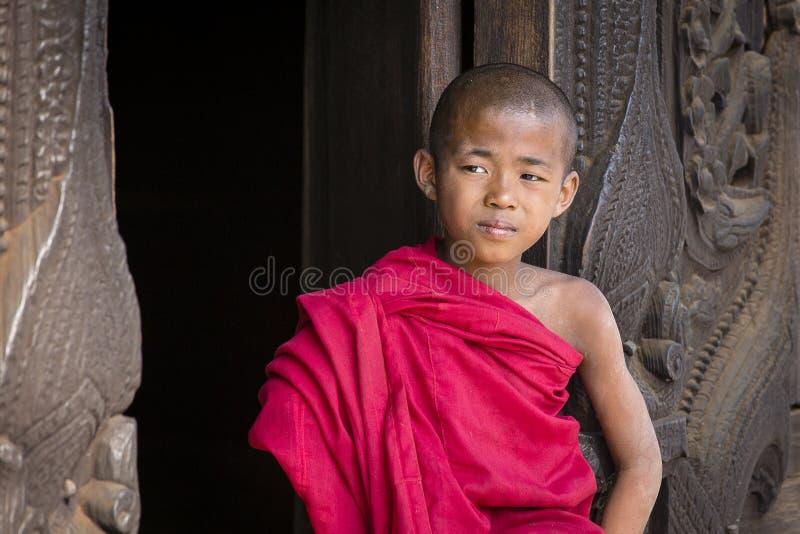 Młody michaelita obsiadanie i patrzeć Shwenandaw monaster Mandalay, Birma, Myanmar obraz stock