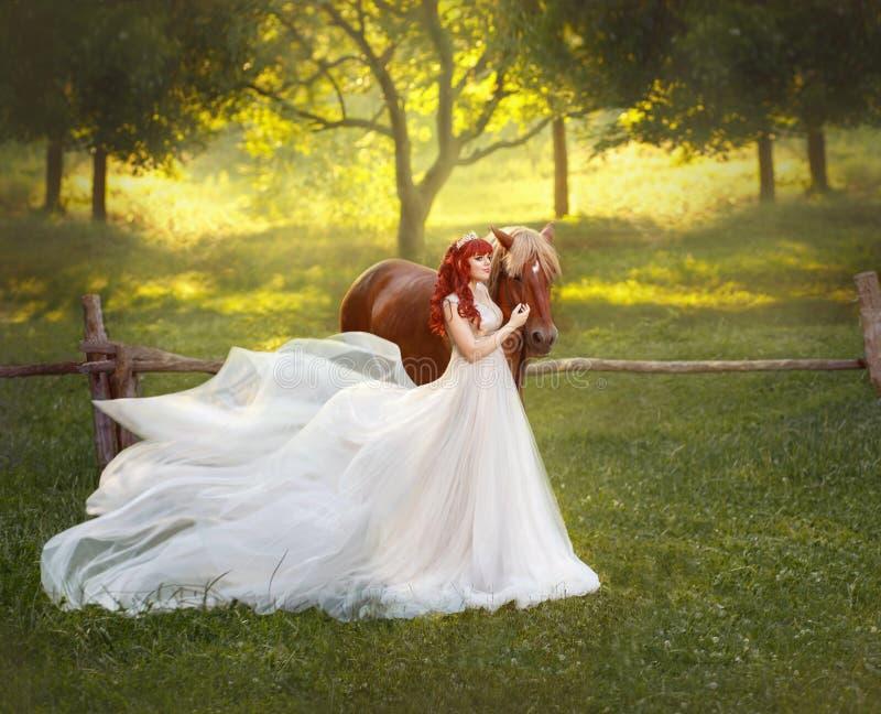 Młody, miedzianowłosy princess w krystalicznej tiarze, ściska jej konia i muska Tło jest fantastycznym lasowym halizną zdjęcia royalty free