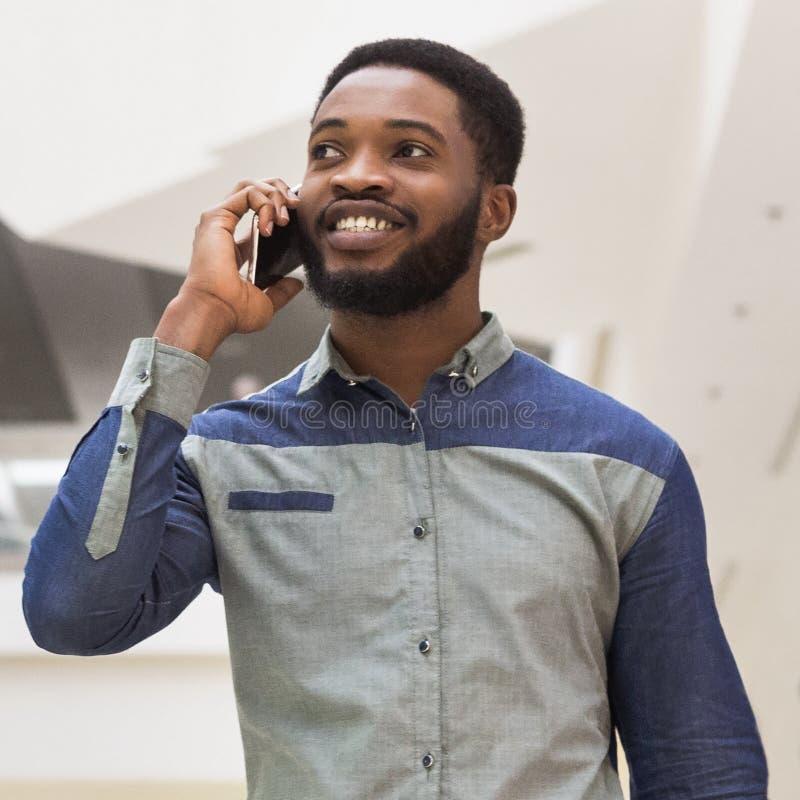 Młody millennial afrykański mężczyzna opowiada na telefonie obrazy royalty free