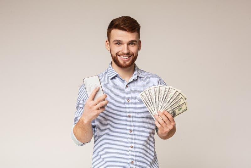 Młody millennial facet robi pieniądze online na jego telefonie komórkowym zdjęcie stock