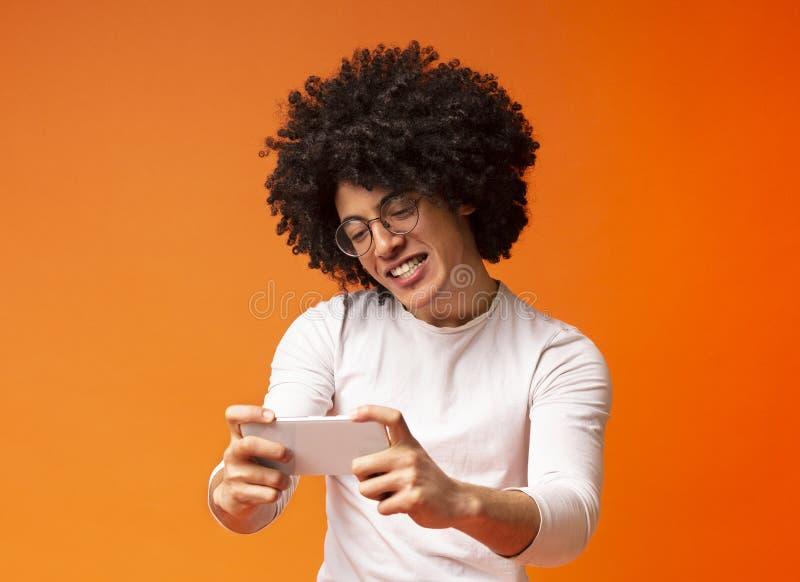 Młody millennial mężczyzna bawić się gra wideo, używać mobilnego zastosowanie zdjęcia royalty free