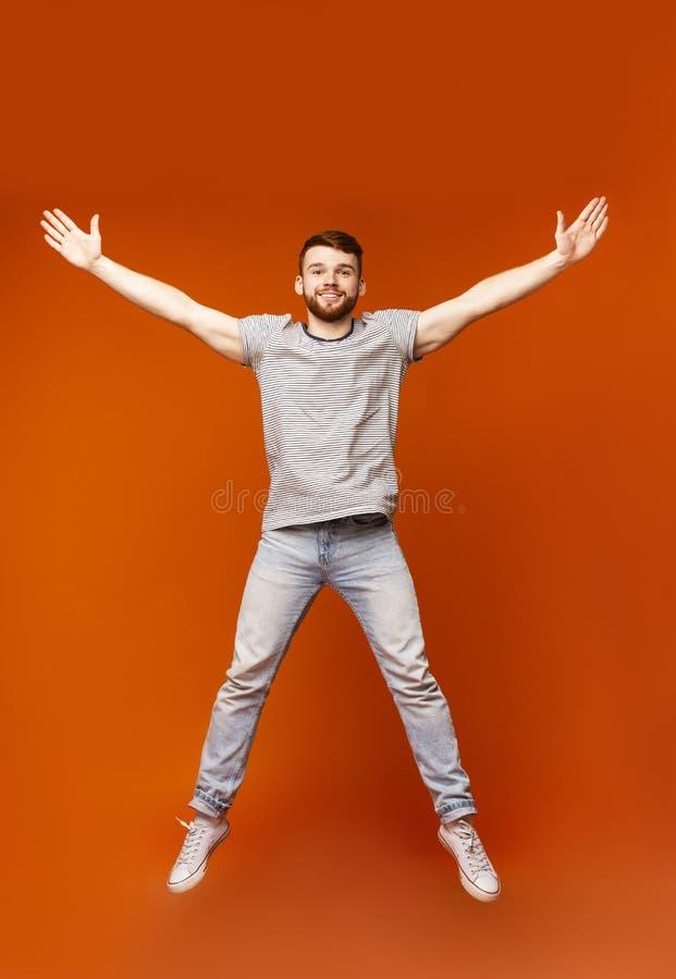 Młody millennial mężczyzny doskakiwanie z otwartymi rękami zdjęcie stock