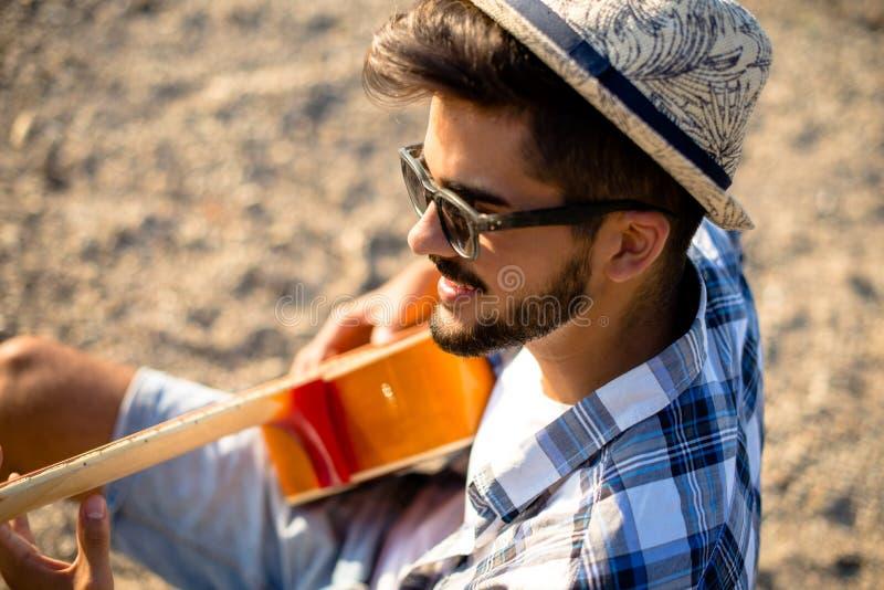 Młody modniś bawić się gitarę zdjęcie stock