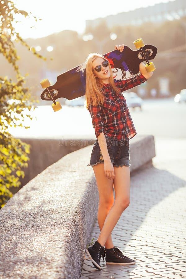 Młody modniś kobiety mienia deskorolka za głową w zmierzchu, outdoors, filmowy styl Elegancka szczęsliwa modniś kobieta fotografia stock