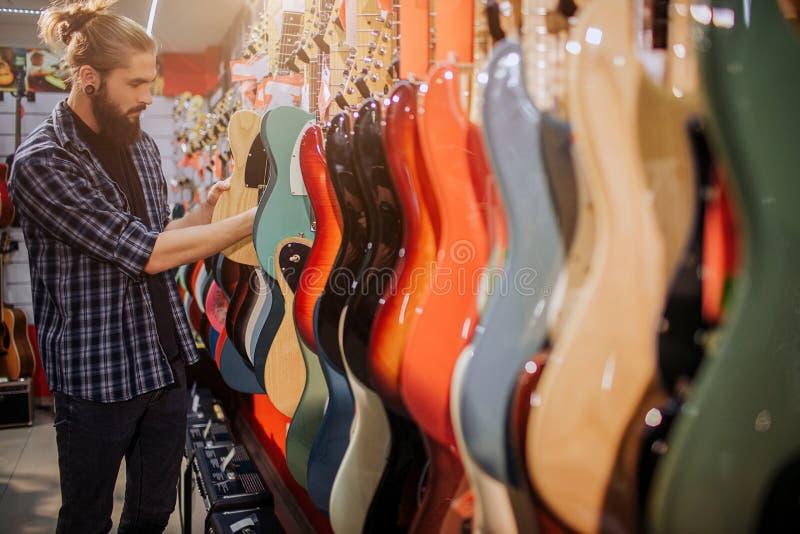 Młody modniś z długie włosy w górę stojaka przed eklektycznym gitary andtouch one Wybiera Mężczyzna wewnątrz samotnie w pokoju du obraz royalty free