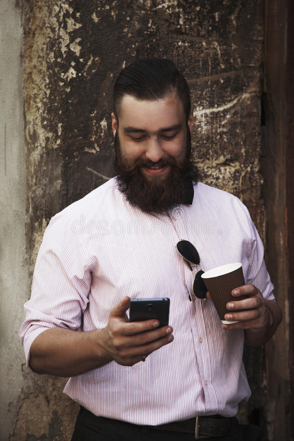 Młody modnisia biznesmen z brody mienia telefonem i kawą zdjęcie royalty free