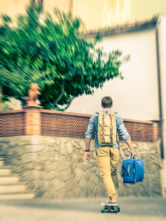 Młody modnisia mężczyzna chodzenie z jego bagażem i longboard zdjęcia royalty free