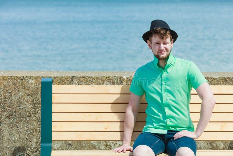 Młody modnisia mężczyzna obsiadanie na ławce blisko morza plenerowego zdjęcie stock