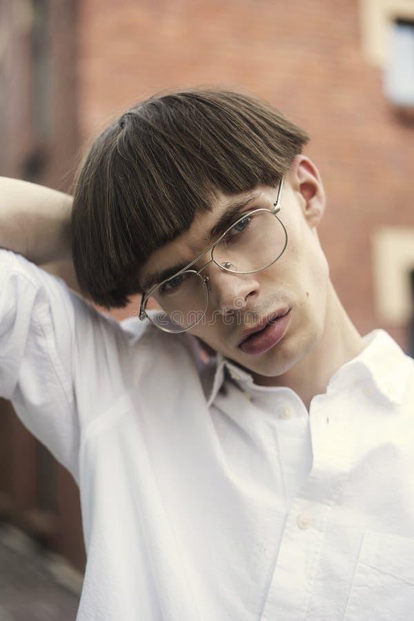 Młody modnisia mężczyzna w ulica stylu mody pojęciu Facet jest ubranym eleganckich szkła jest ubranym białą koszula Wzorcowy m??c zdjęcia royalty free
