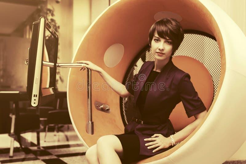 Młody mody biznesowej kobiety obsiadanie na komputerowym krześle w biurze obrazy royalty free