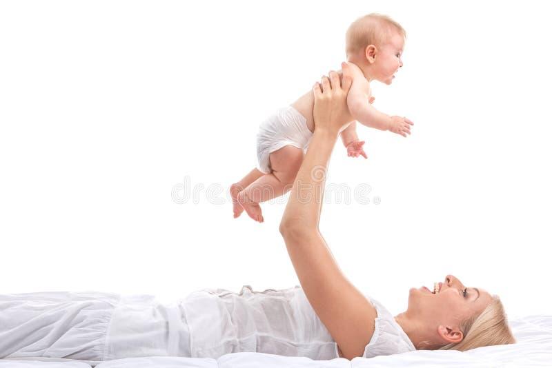 Młody mum trzyma małego dziecka piękny blond podnośny dziecko up i uśmiechnięty zdjęcia royalty free