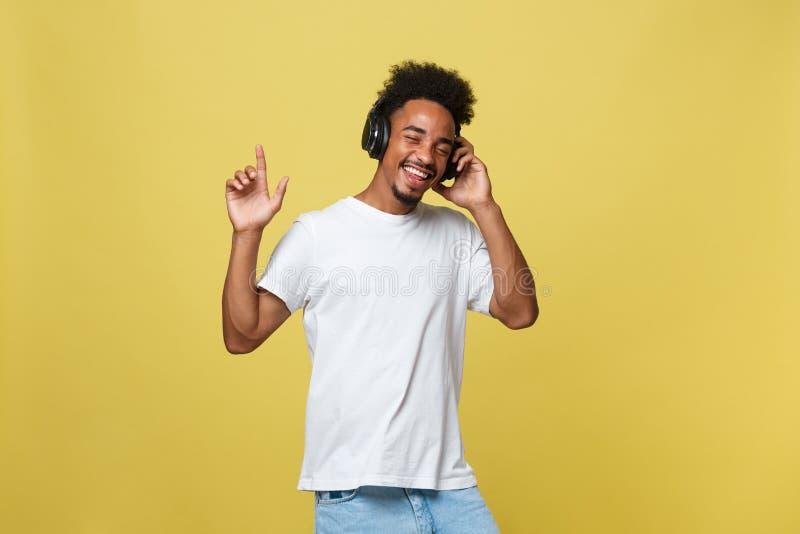 Młody murzyn target222_1_ muzyka nad jego hełmofonami Odizolowywający nad żółtym tłem zdjęcia royalty free