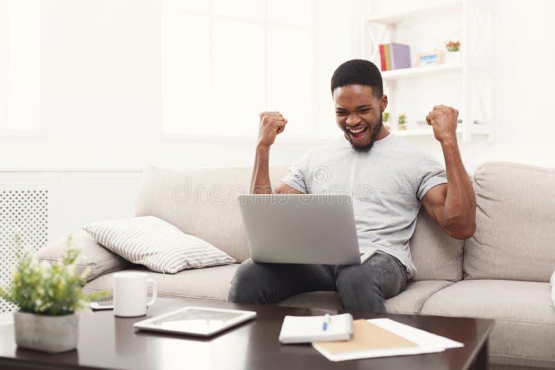 Młody murzyn z nastroszonymi rękami z laptop odświętności sukcesem, obrazy stock