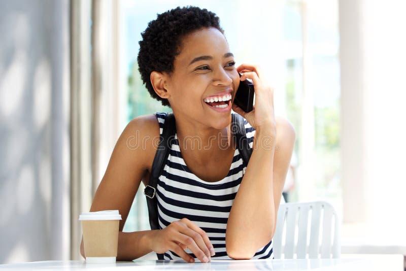 Młody murzynki obsiadanie przy kawiarnią opowiada na telefonie komórkowym zdjęcia stock