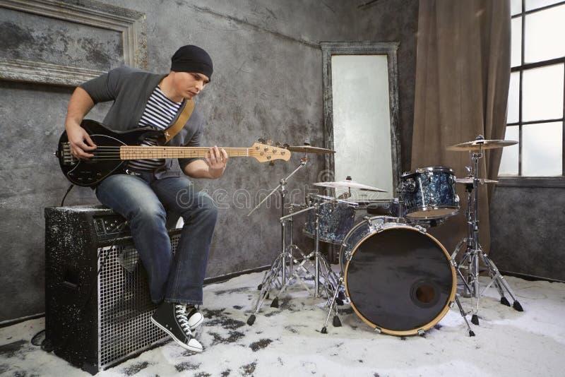 Młody muzyk bawić się basowego gitary elektrycznej obsiadanie na amplifikatorze obraz royalty free